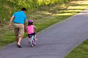 Child learning to ride a bicycle with father @ ClickImages